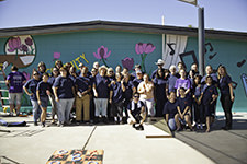 Volunteers stand in front of the finished wall mural designed and drawn by Dale Hunnewell, a former student at the Art Institute of Phoenix (Photo credit: SHAVON ROSE/AZ Big Media)